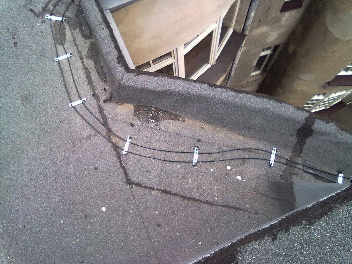Instalacje anty-oblodzeniowe - elektryk biega po dachu
